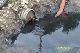 Water being colledted for pumping back to wet side of pond.  Note color and heavy oil sheen.